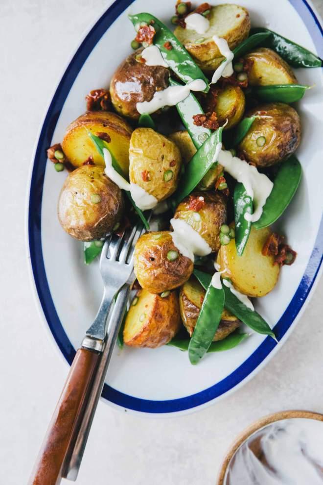 Krompirjeva solata z mladim grahom, postrežena s slastnim prelivom