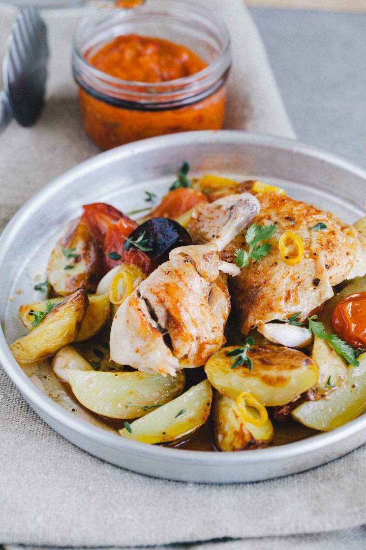 Pečen piščanec z mladim krompirjem postrežen na krožniku s paradižnikom