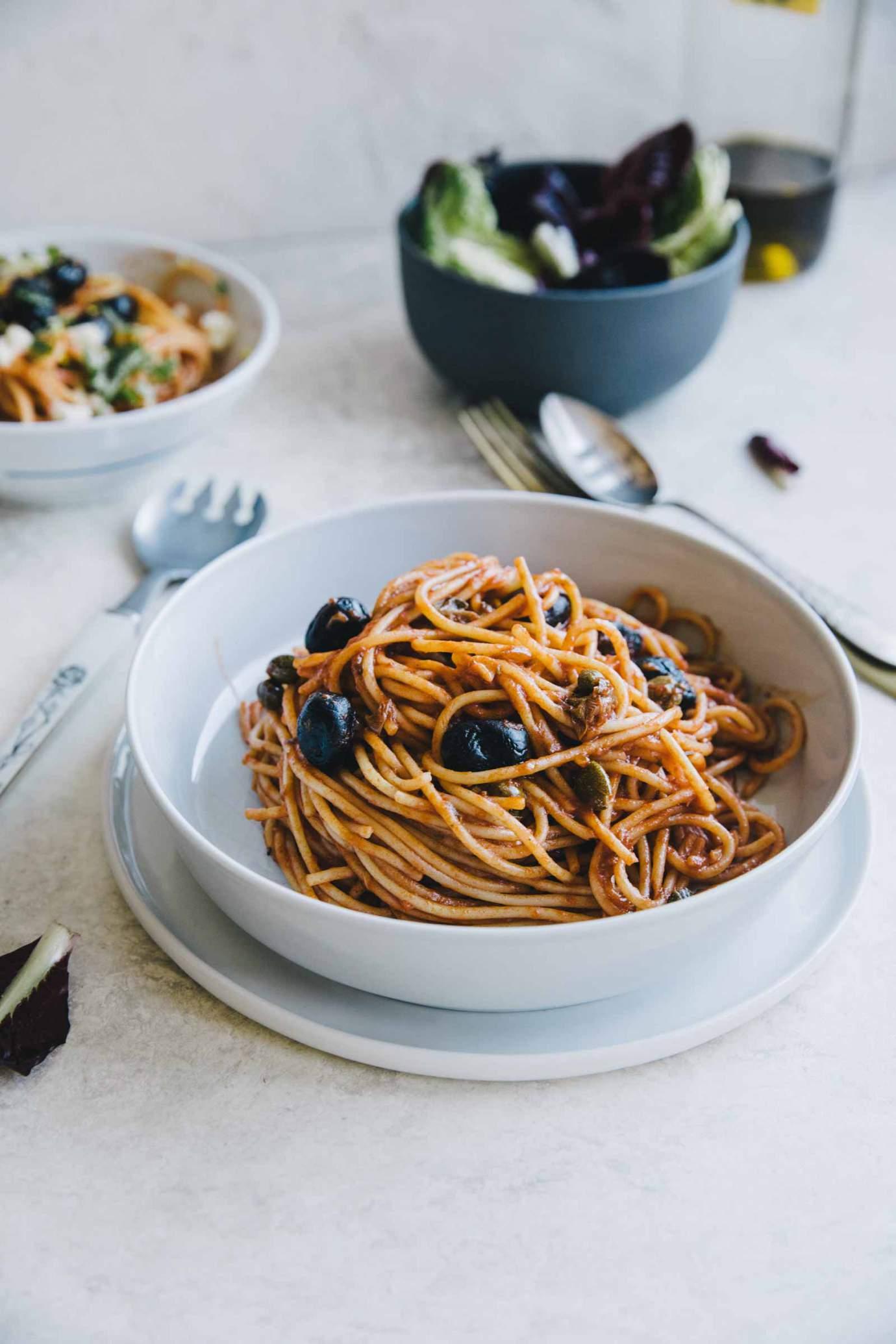 Spaghetti alla Puttanesca served in a bowl with parsley and mozzarella