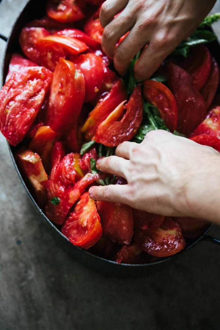 Stirring tomatoes in a pot for Homemade Simple Tomato Purée