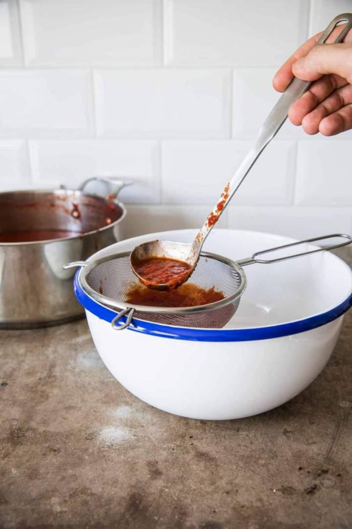 Straining Homemade Simple Tomato Purée through a sieve